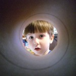 Christoper looks through a circular tube